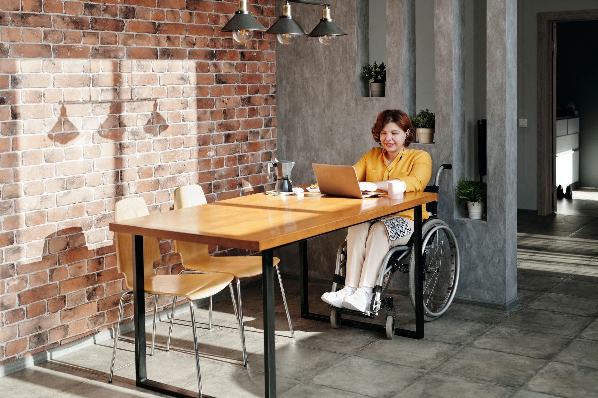 Kvinne i rullestol sitter ved et bord.