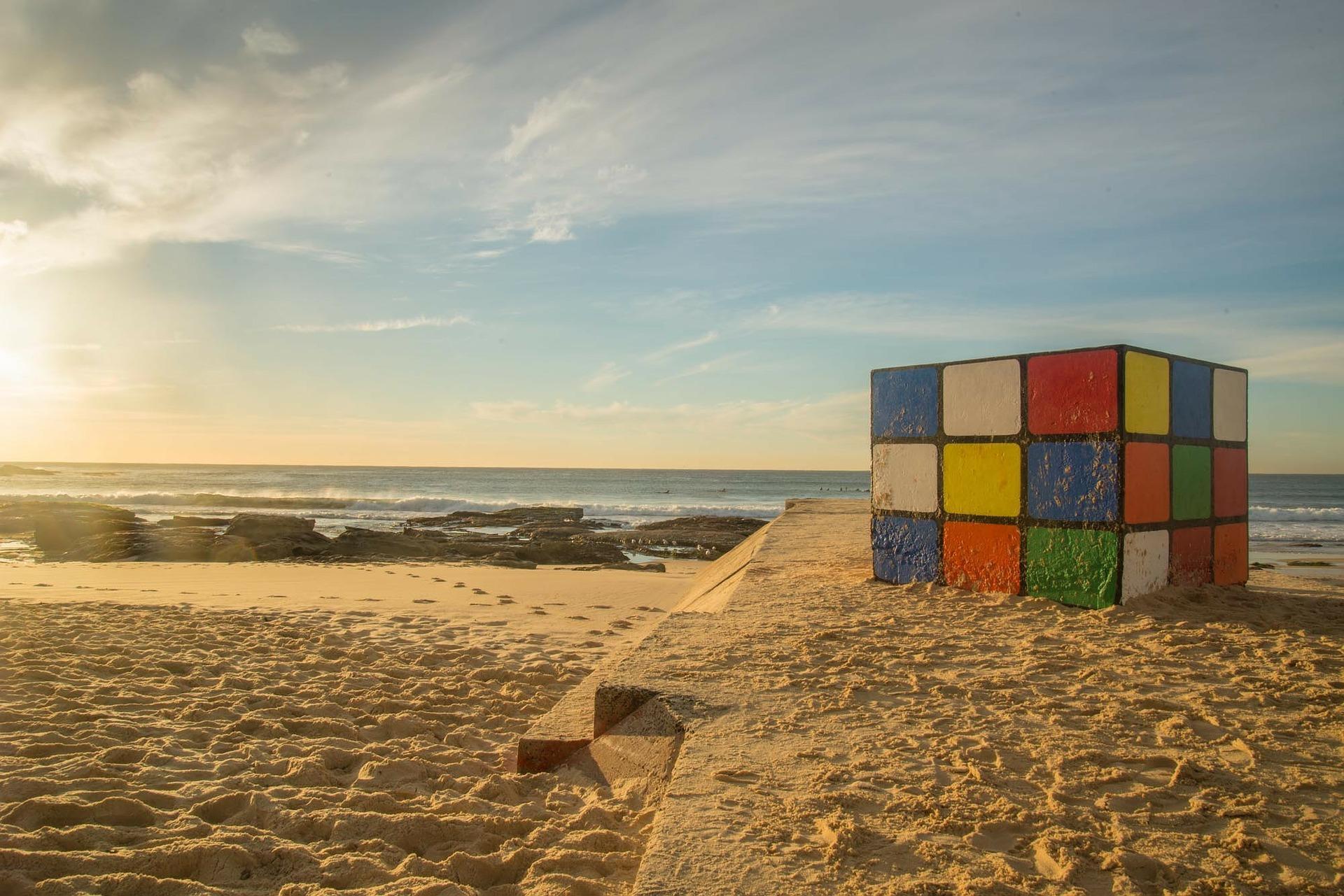En stor Rubiks kube på en sandstrand