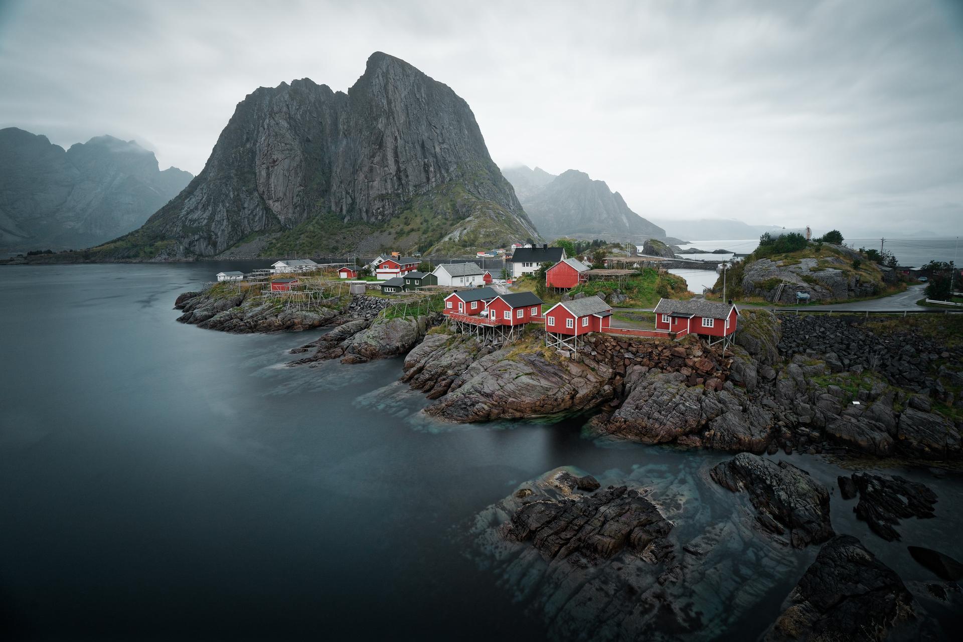 Høyt fjell og flere hus i sjøkanten.