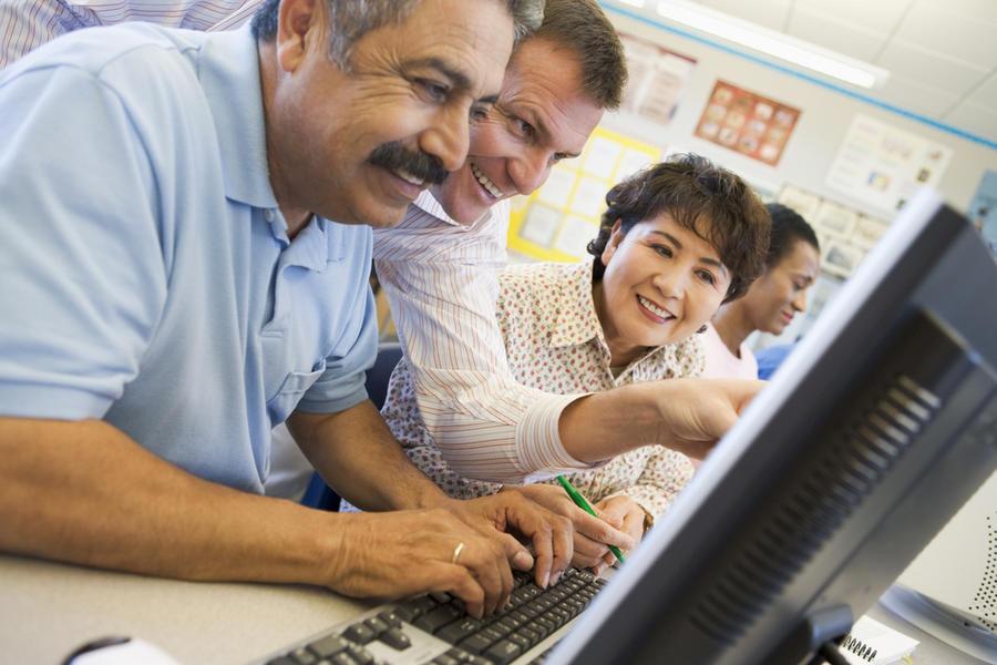 Flere mennesker sitter foran en laptop og lærer hvordan å bruke den.