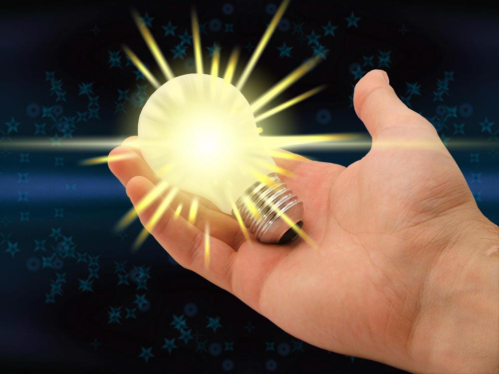 Hånd som holder en glødende lyspære.