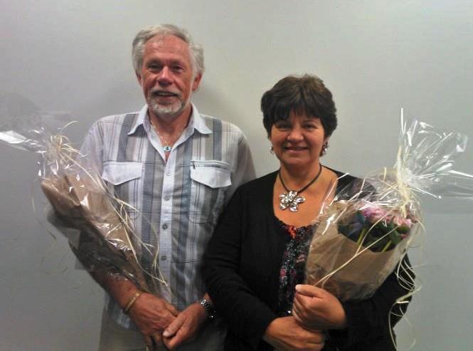 Mann og kvinne står ved siden av hverandre, med hver sin blomsterbukett i favnen.