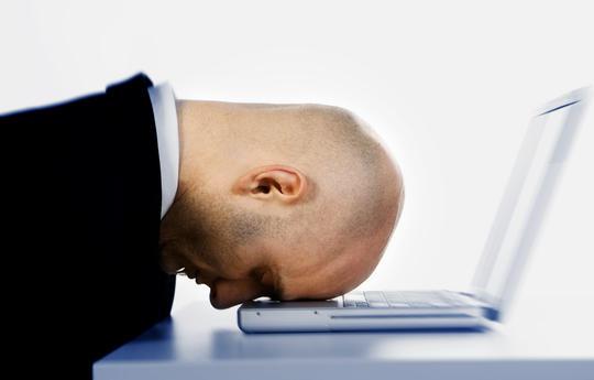 Mann som stanger hodet i en laptop.