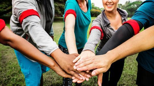 Flere folk som holder på hverandres hender.
